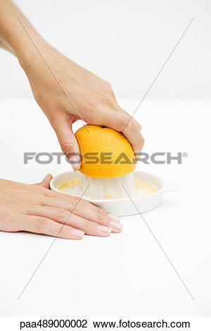 Stock Photo of Woman squeezing orange with citrus press, cropped.