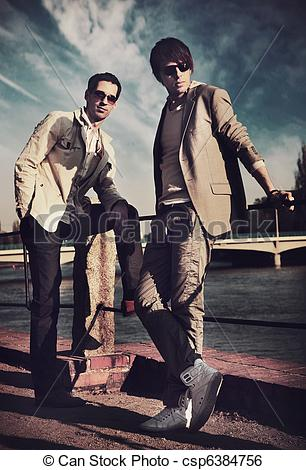 Stock Image of Two handsome friends posing on a city promenade.
