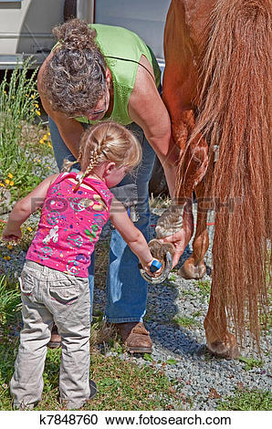 Stock Photography of Woman Helps Toddler Clean Horse Shoe k7848760.