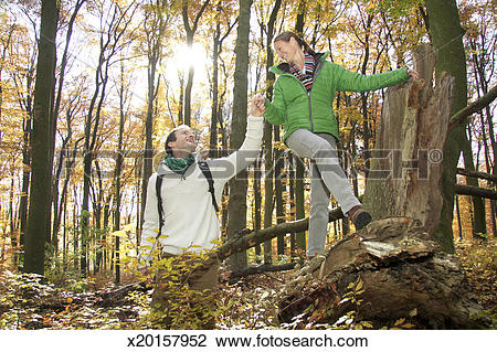 Stock Photo of Mid adult man holding hand of woman climbing over.