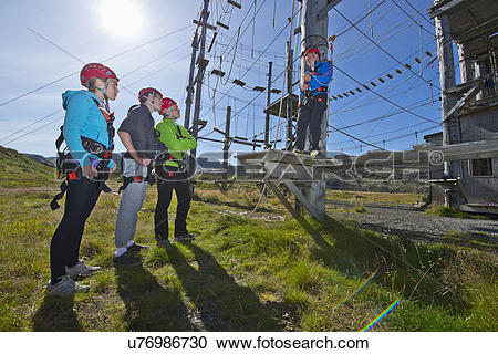 Stock Photography of Four people wearing climbing helmets on high.