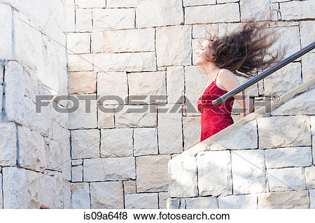 Pictures of Woman climbing stone steps outdoors is09a64f8.