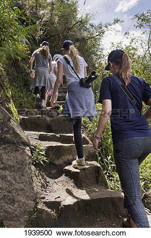 Stock Photography of Girls Climbing Stone Steps At Machu Picchu.