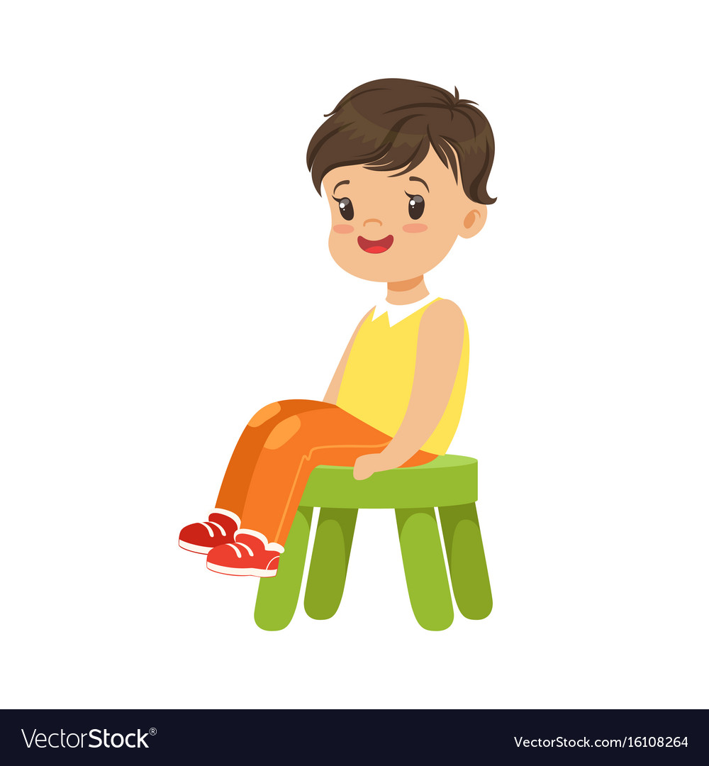 Cute little boy sitting on a small green stool.