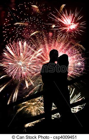 Stock Photography of A silhouette of a kissing couple in front of.