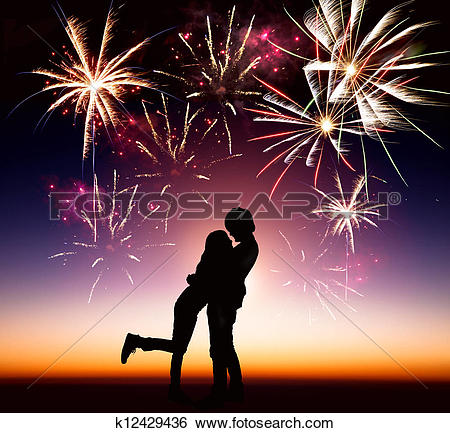 Stock Images of happy young couple with fireworks background.