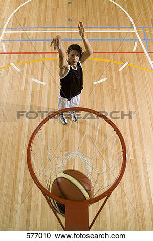 Stock Photography of A young man shooting a basketball into a.