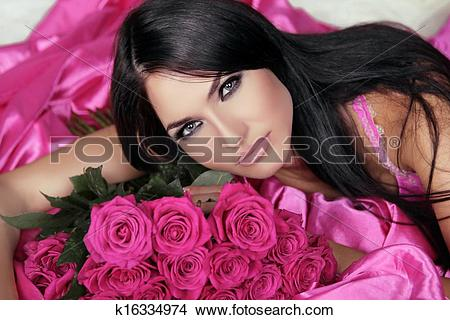 Stock Photo of Beauty portrait of brunette girl with pink Roses.