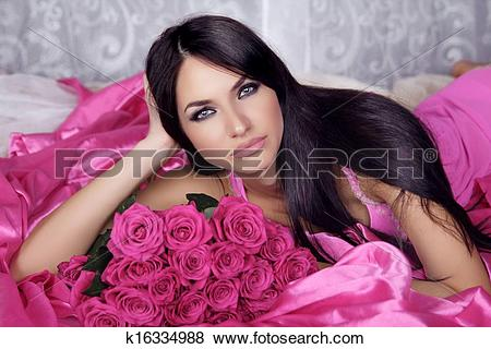 Pictures of Beauty portrait of brunette girl with pink Roses lying.