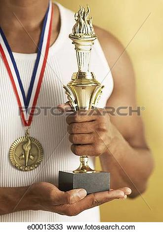 Stock Photo of Man wearing gold medal and holding trophy e00013533.