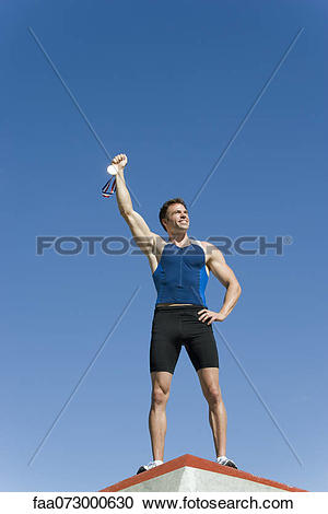 Stock Photography of Male athlete on podium, holding up gold medal.