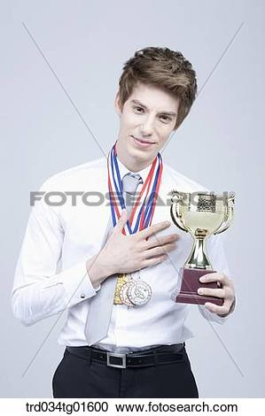 Stock Photography of A man holding the prize medal and trophy.