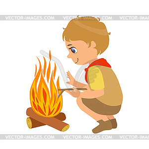 Boy scout squatting near bonfire, colorful character.