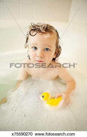 Stock Photography of A wet toddler looks at the viewer while.