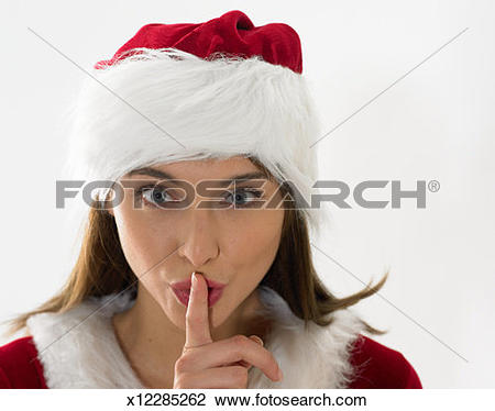 Stock Photo of Young woman in santa suit with finger over lips.