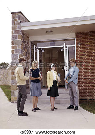 Picture of 1960s teen students standing at entrance to school boys.