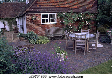 Stock Images of Wooden chairs and table on brick patio in front of.