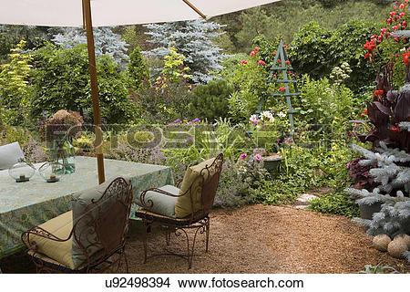 Stock Photo of GARDEN: Wild, gravel path/patio, cannas, roses on.