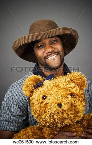 Stock Photography of Young black man wearing a hat and holding a.