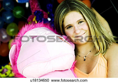 Stock Photography of Girl at carnival holding stuffed animal.