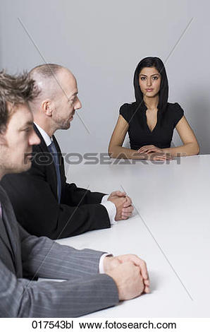 Stock Photo of young woman sitting at conference table with two.