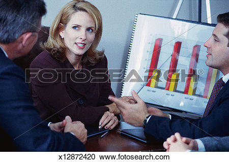 Stock Photography of Woman and men at conference table; woman.