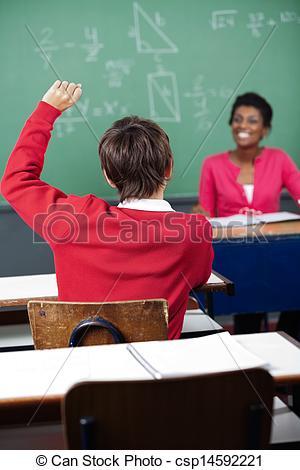 Stock Photo of Teenage Schoolboy Raising Hand At Desk.