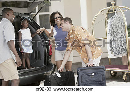 Stock Photo of Hotel employee helping family unload car. pr92783.