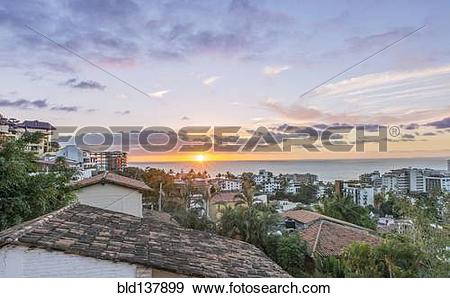 Stock Photograph of Aerial view of city rooftops, sunrise and.