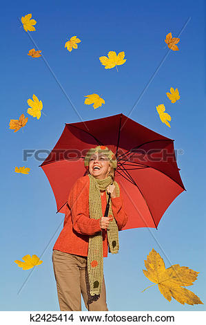 Stock Photo of Happy woman with umbrella and falling yellow leaves.