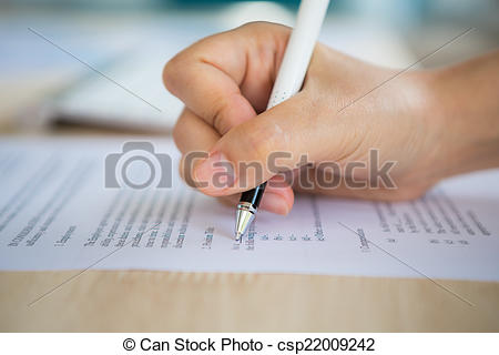Stock Photo of Close up of hand completing an employment.