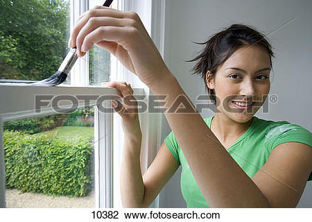 Stock Photo of Young woman painting window frame, smiling.