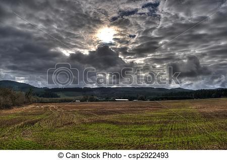 Stock Photos of Empty Grass Field With Sun Bursting Through A Dark.