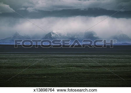 Stock Photo of Rugged mountains in cloud cover behind gassy field.