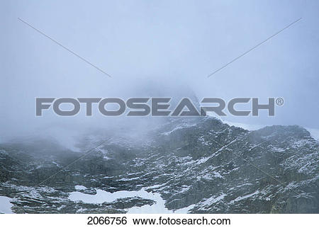 Stock Images of Mountain Ridge With Cloud Cover And Snow Patched.