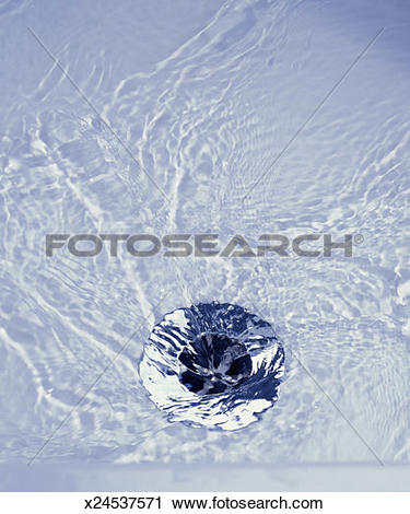Stock Photography of Water running down plug hole, close.