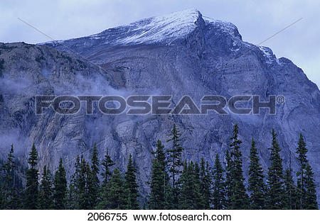 Stock Image of Mountain Ridge With Cloud Cover And Snow Patched.
