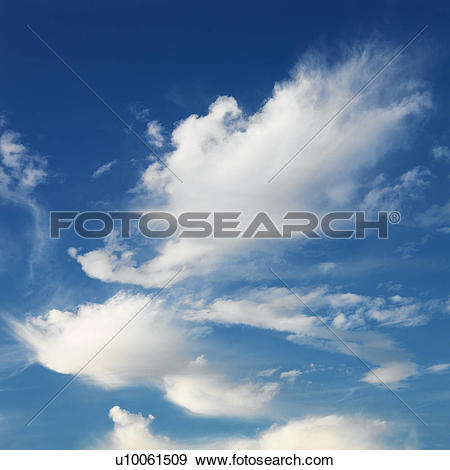Stock Photograph of Wispy cloud formations against clear blue sky.