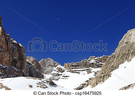 Stock Photo of Snowy rocks and cloudless blue sky with moon.