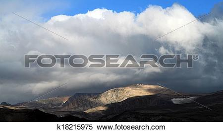 Stock Image of Storm clouds gathering over a mountain range.