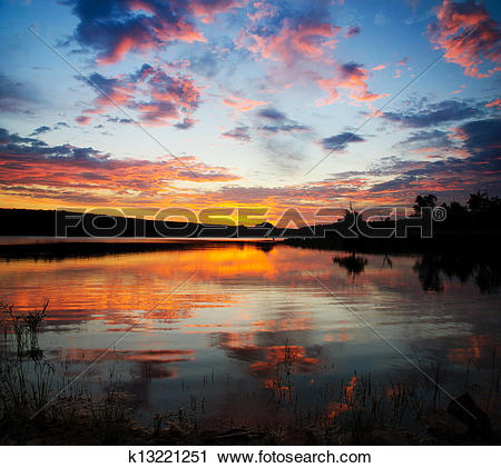 Stock Photography of Striking sunset above lake with bright clouds.