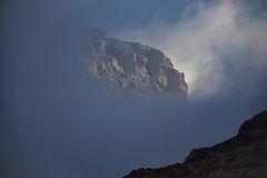 Mountain Top Peeking Through Clouds Stock Photos.