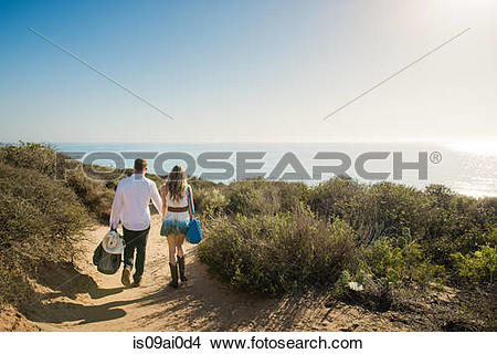 Stock Photo of Romantic young couple strolling on coastal path.