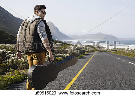 Stock Photograph of Rear view of young man walking on coastal road.
