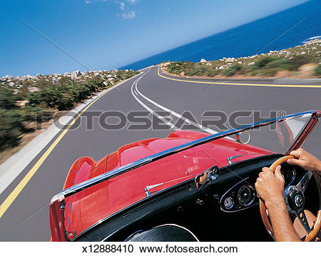 Stock Photography of Man Driving Red Sports Car on Coastal Road.