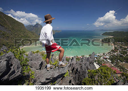 Stock Photograph of Man Enjoys View From Limestone Spires Over.