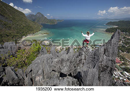 Stock Photography of Man Enjoys View From Limestone Spires Over.