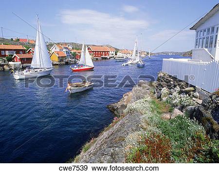 Stock Photograph of Sailboats passing coastal village of Kyrkesund.