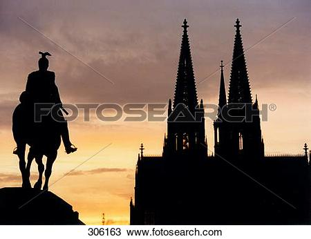 Stock Photo of Silhouette of sculpture and church against dusky.