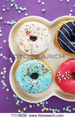 Stock Image of Four doughnuts with colourful glaze and sugar.